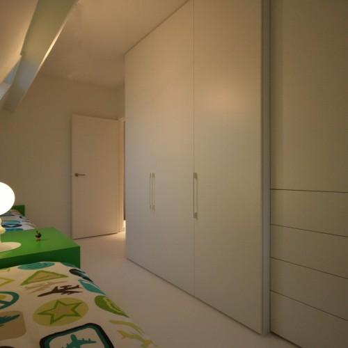 in deze slaapkamer werd een strakke kastenwand geplaatst om het geheel strak te houden werden